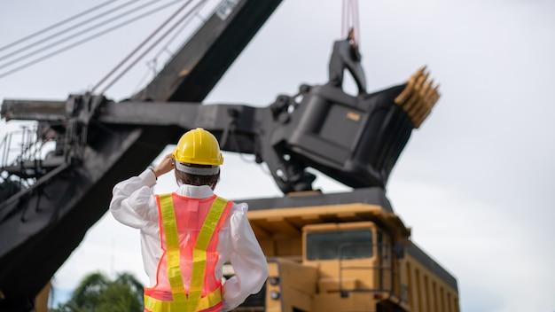 Trabalhador na mineração de lignito ou carvão com o caminhão transportando carvão.