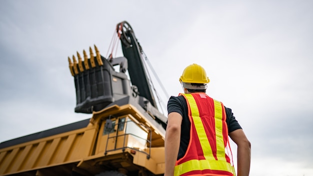 Trabalhador na mineração de linhita ou carvão com o caminhão transportando carvão.