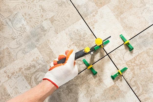 Trabalhador nivelando o ladrilho de cerâmica com cunhas e clipes