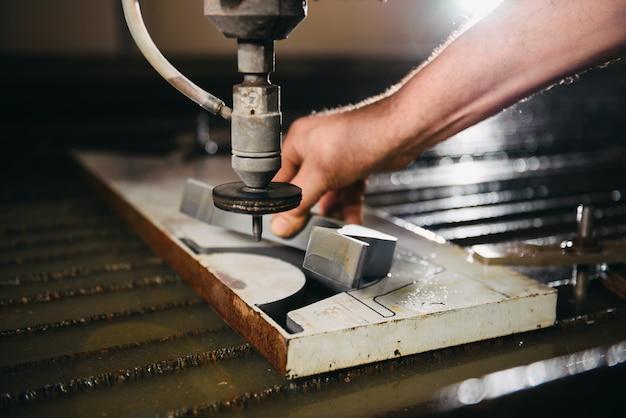 Trabalhador no cortador de jato de água leva seção de corte