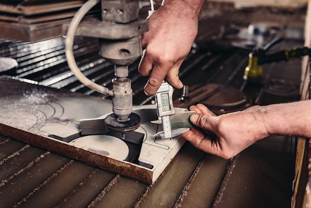 Trabalhador no cortador de jato de água, verificando medidas com paquímetro digital