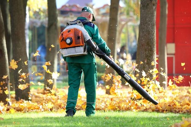 Trabalhador no parque limpa a grama das folhas caídas com a ajuda de uma turbina eólica