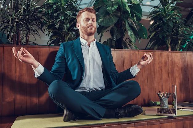 Trabalhador no terno que medita no banco no escritório.