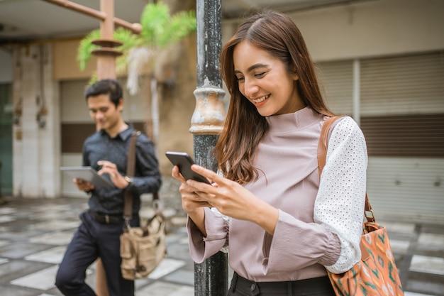 Trabalhador ocupado usando seu gadget enquanto espera pelo transporte público