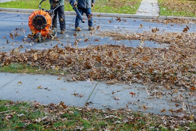 Trabalhador operando soprador de folhas de serviço pesado na remoção de folhas caídas em dias de outono