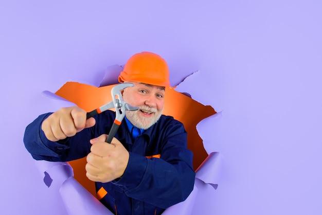 Trabalhador ou construtor em capacete com um alicate olhando através de papel. encanador profissional segura um alicate automático