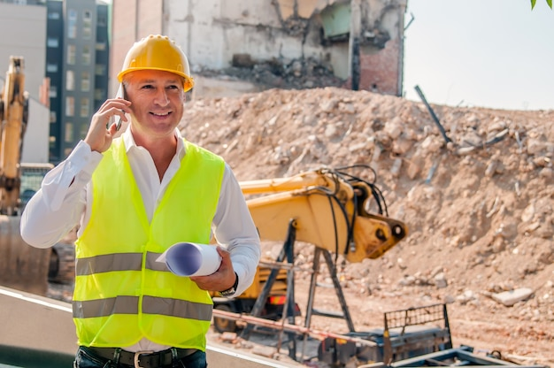 Trabalhador ou engenheiro segurando o capacete das mãos para a segurança dos trabalhadores no fundo de novos prédios de apartamentos highrise e guindastes de construção em segundo plano.