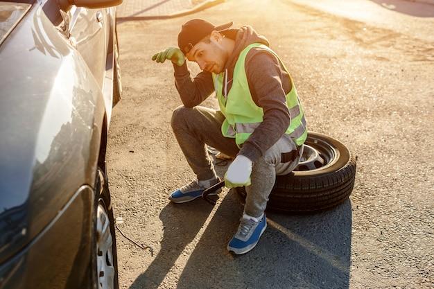 Trabalhador ou motorista cansado de consertar um carro na berma da estrada