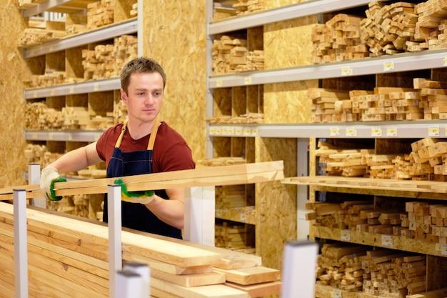 Trabalhador ou vendedor na seção de madeira da loja ou armazém de construção no trabalho