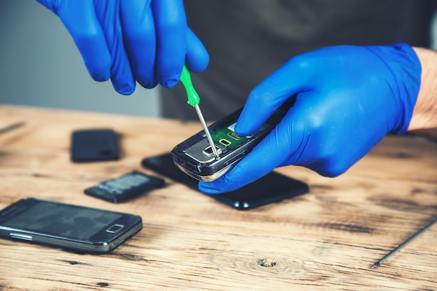 Trabalhador para consertar telefone inteligente na mesa de madeira