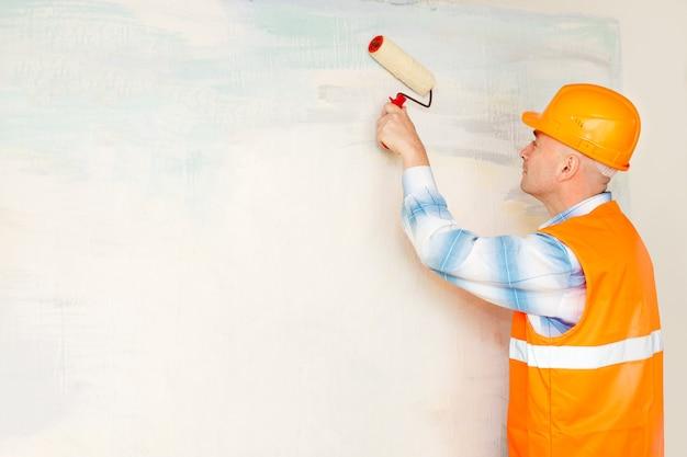 Trabalhador pinta um rolo de parede para pintar
