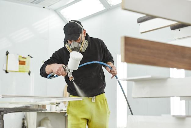 Trabalhador pintando detalhes de móveis usando pistola, o carpinteiro pinta detalhes de móveis