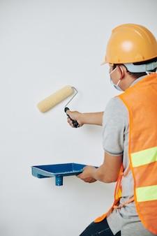 Trabalhador pintando paredes de branco
