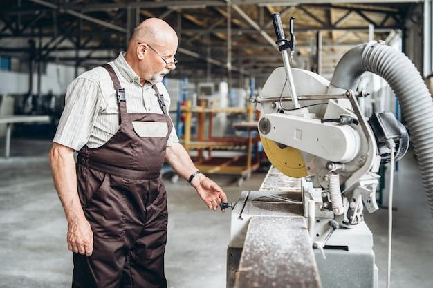 Trabalhador profissional adulto na fábrica trabalhando com máquinas.