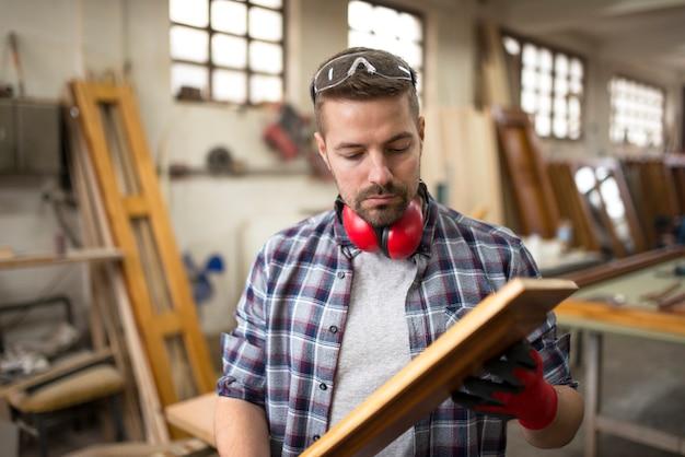 Trabalhador profissional carpinteiro verificando a qualidade do produto de madeira na oficina de carpintaria