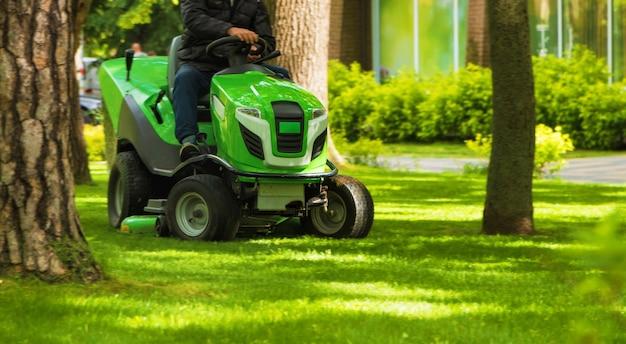 Trabalhador profissional cortando a grama verde com o trator cortador de grama no parque. conceito de cuidado do gramado.