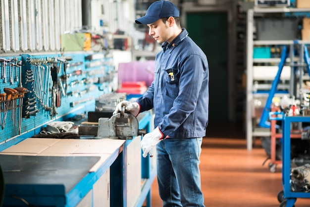 Trabalhador, protegendo uma placa de metal em um torno