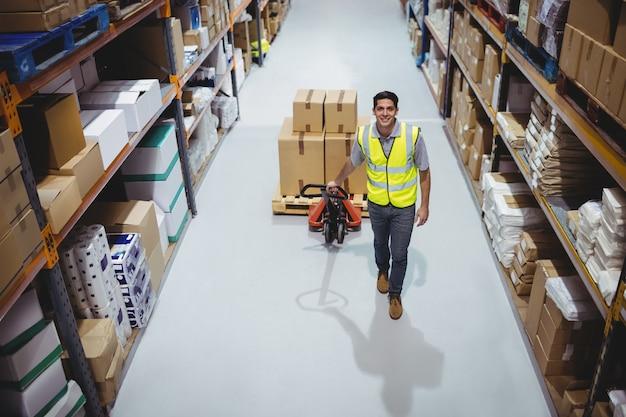 Trabalhador, puxando o carrinho com caixas no armazém