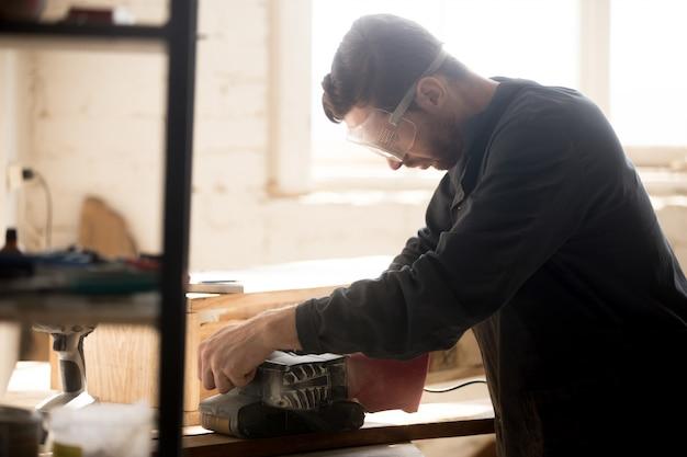 Trabalhador qualificado e experiente trabalhando com lixadeira para moagem de madeira, dentro de casa