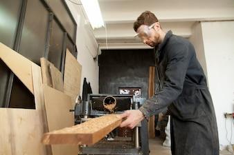 Trabalhador qualificado trabalhando em tábua de madeira em planadora de energia para trabalhar madeira
