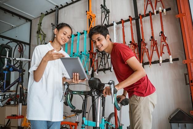 Trabalhador que atende um cliente usando um tablet digital enquanto faz compras na loja de bicicletas