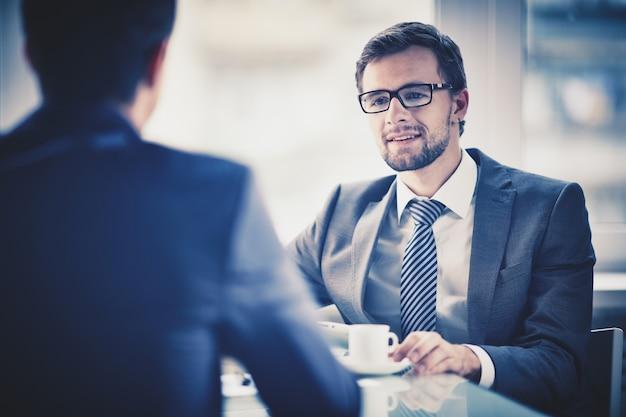 Trabalhador que bebe uma chávena de café com um colega