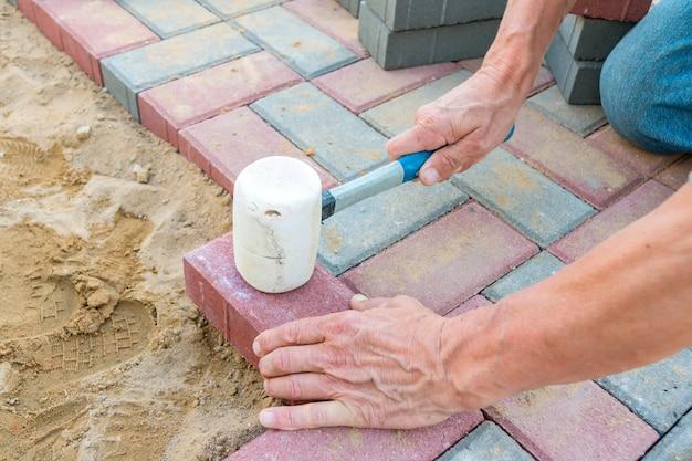 Trabalhador que coloca blocos de pavimentação concretos vermelhos e cinzentos. pavimentação de estradas, construção.