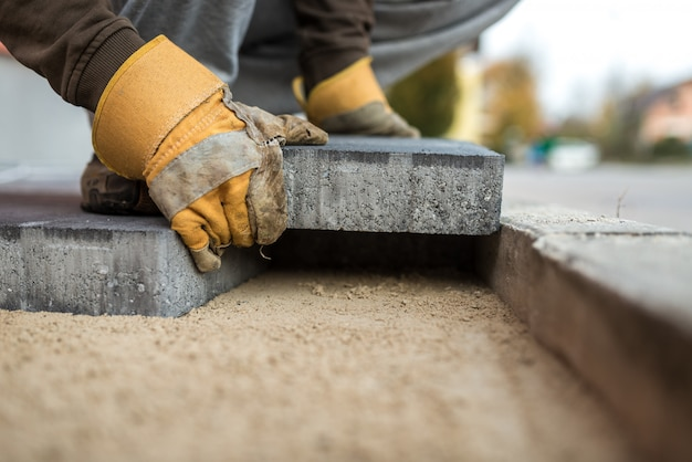 Trabalhador que coloca pedras de pavimentação exteriores