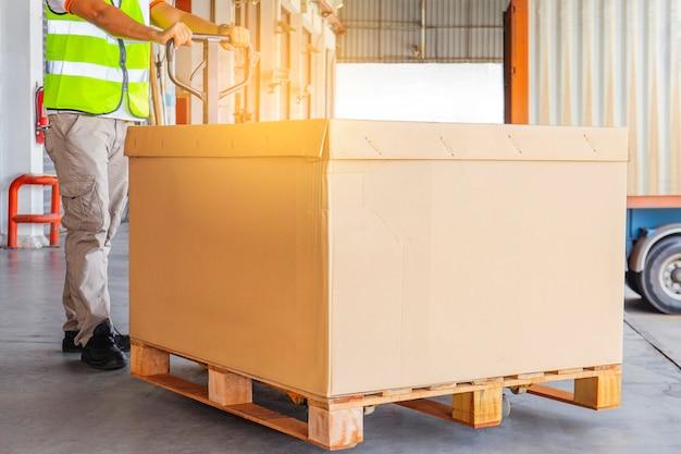 Trabalhador que descarrega carga pesada de paletes com o contêiner de caminhão