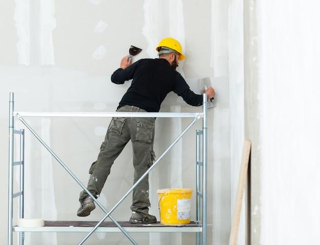 Trabalhador que emplastra a parede da placa de gipsita.