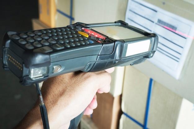 Trabalhador que escaneia o scanner de código de barras na caixa da embalagem ferramenta de trabalho do computador para gerenciamento de estoque do armazém