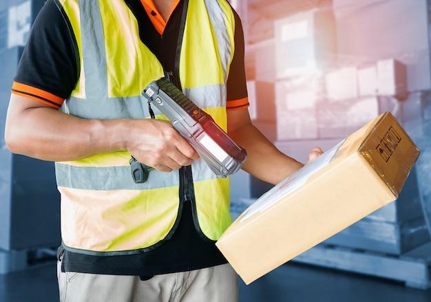 Trabalhador que escaneia o scanner de código de barras na caixa de embalagem ferramenta de trabalho de computador para gerenciamento de estoque de armazém