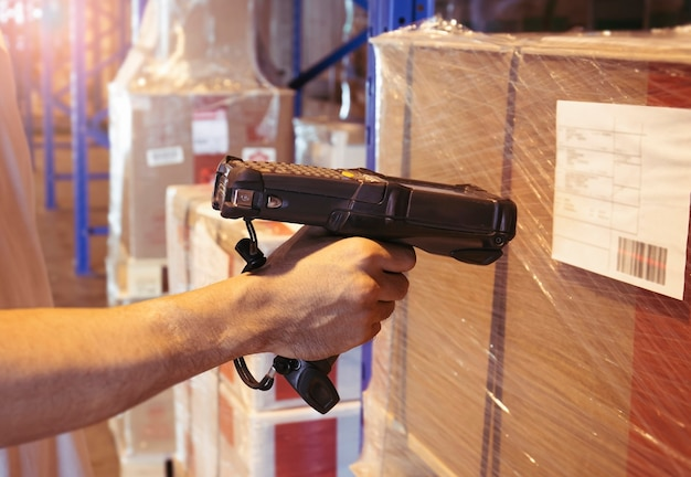 Trabalhador que faz a varredura de scanner de código de barras nos produtos no armazém.