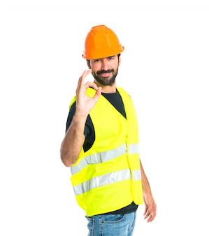 Trabalhador que faz ok assina sobre fundo branco