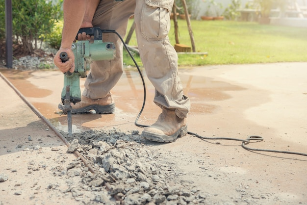 Trabalhador que fura a entrada de automóveis concreta com o jackhammer.