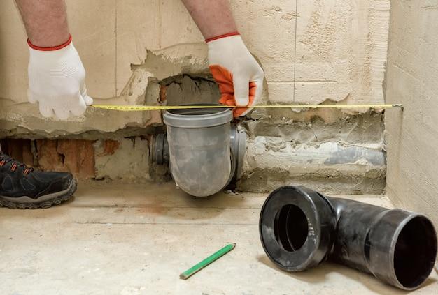 Trabalhador que instala um tubo de drenagem de esgoto para instalar o tanque embutido do vaso sanitário