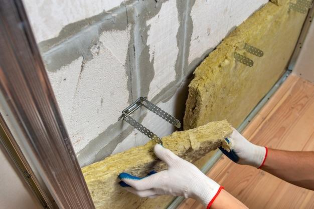 Trabalhador que isola uma parede da sala com isolamento térmico de lã de rocha mineral.