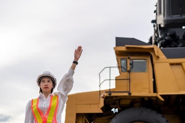 Trabalhador que levanta a mão dá um sinal em linhita ou mineração de carvão com o caminhão transportando carvão.