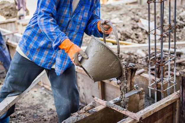 Trabalhador que mistura cimento para construção