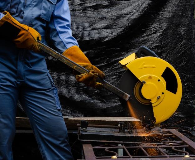 Trabalhador que mói o aço estrutural oco com a ferramenta circular da serra abrasiva