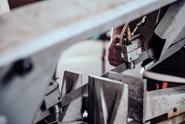 Trabalhador que opera a máquina de corte da serra de fita