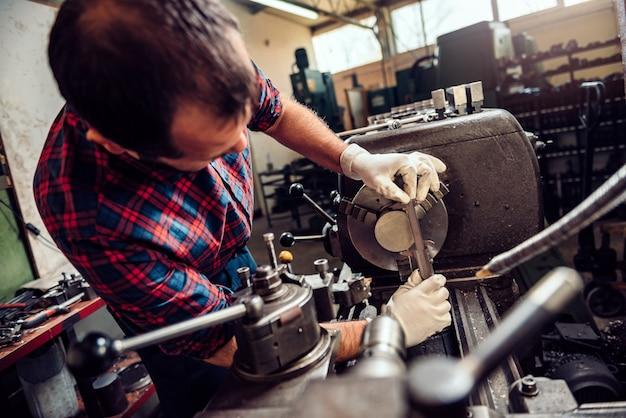 Trabalhador que opera a máquina do torno na fábrica industrial