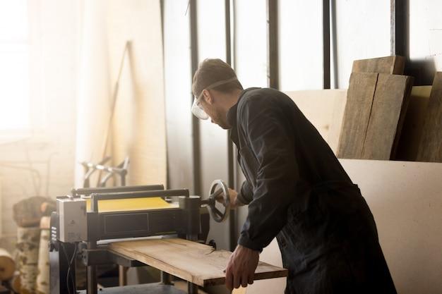 Trabalhador que opera planadora de energia estacionária, processando placa de madeira com máquina