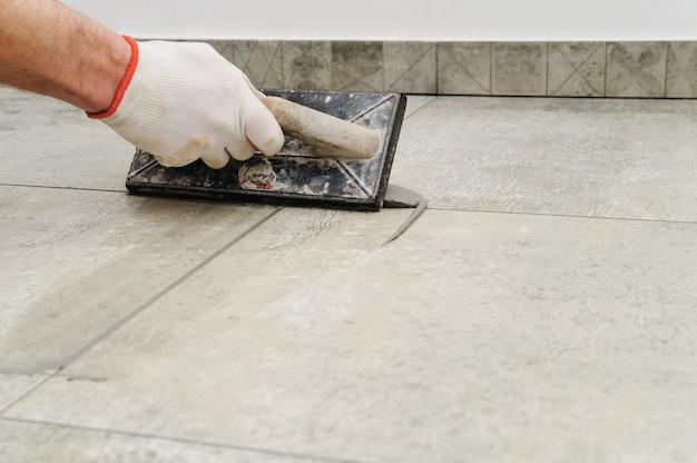 Trabalhador que reboca telhas cerâmicas