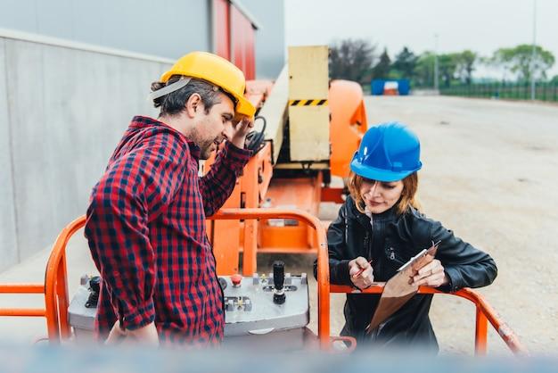 Trabalhador que recebe instruções sobre o elevador reto da lança