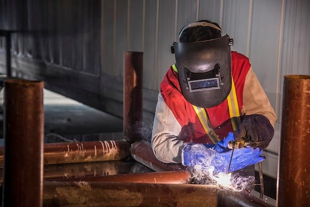 Trabalhador que solda a parte de aço pelo manual no porto