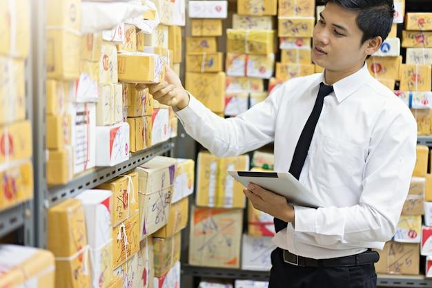 Trabalhador que verifica o pacote usando a tabuleta no armazém.