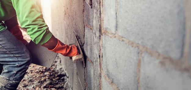 Trabalhador, reboco cimento na parede para construção de casa