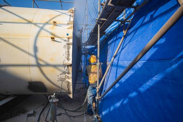 Trabalhador remove tinta do tanque de óleo branco com jato de areia de pressão de ar