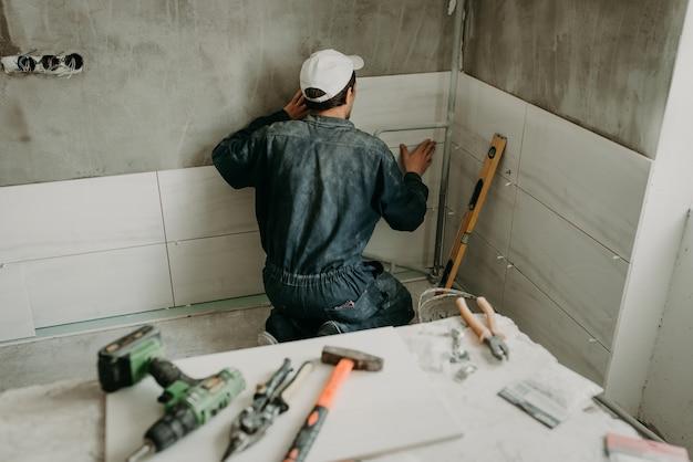 Trabalhador reparador coloca grandes ladrilhos de cerâmica